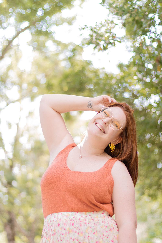 Zoom sur un top orangé et des boucles d'oreilles jaunes, portés avec le sourire pour la rentrée