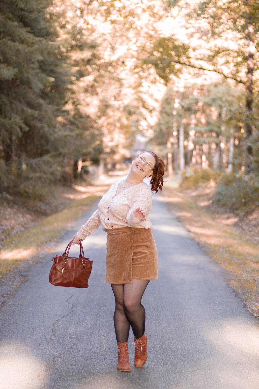 Danse au milieu des bois en tenue d'automne, avec le sourire
