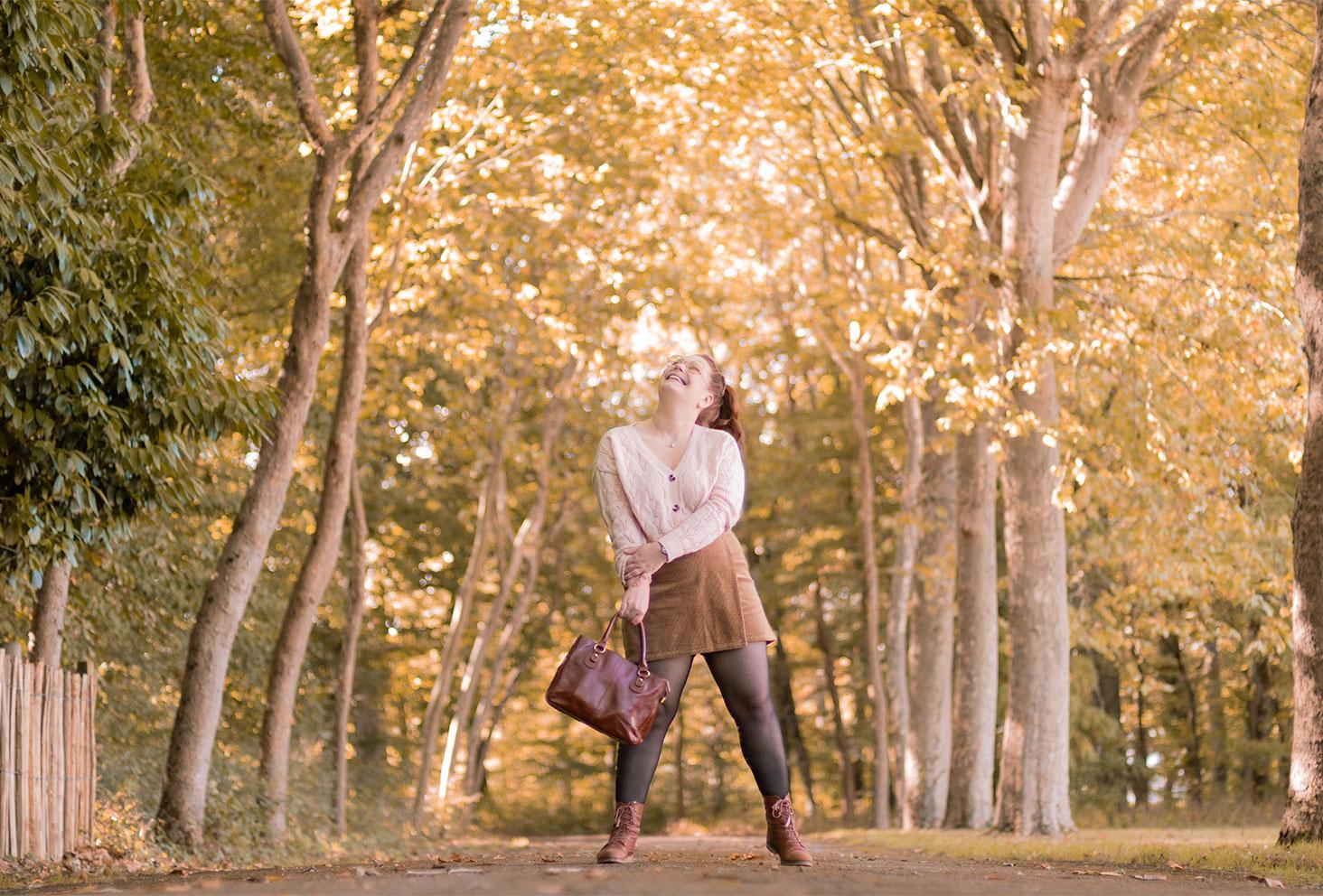 Photo contre-plongée dans la forêt, en gilet et jupe-short marron en velours, avec le sourire et un sac dans les mains