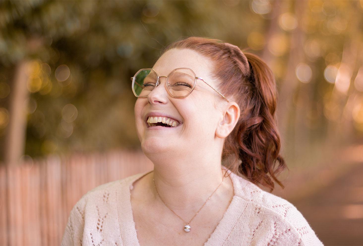 Photo portrait avec le sourire, des lunettes beige et un chouchou en velours dans des cheveux bouclés