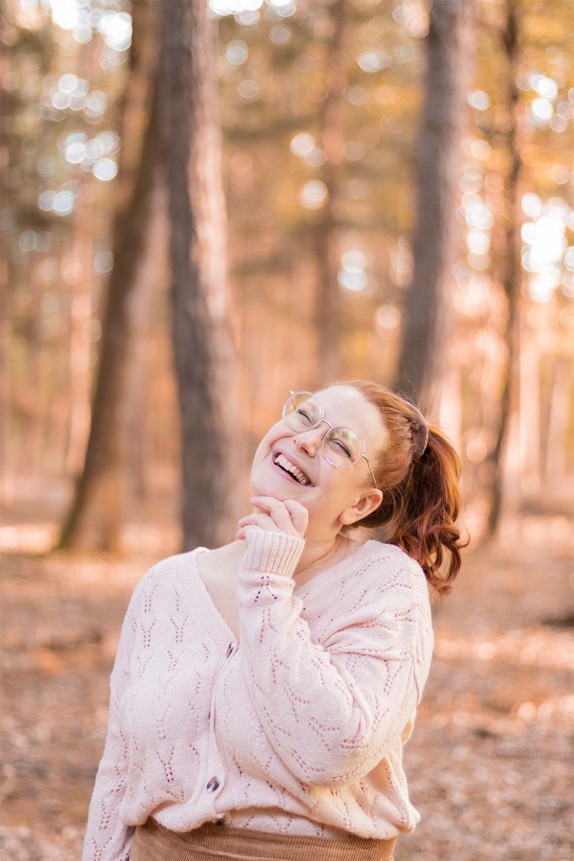 Portrait d'automne avec le sourire, au milieu des bois, une main sous le menton et les cheveux roux attachés