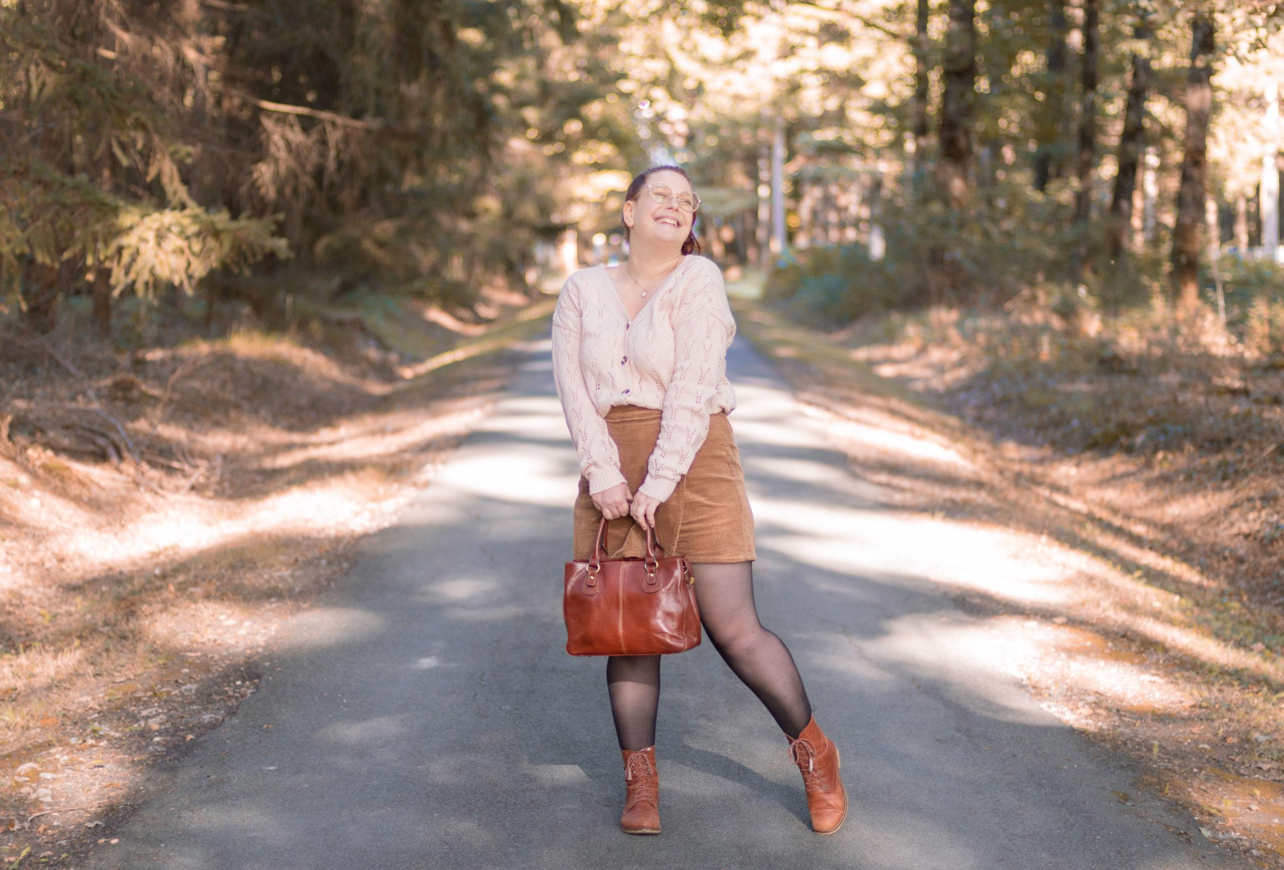 Au milieu des bois en tenue d'automne beige et marron, avec le sourire, un sac en cuir entre les mains