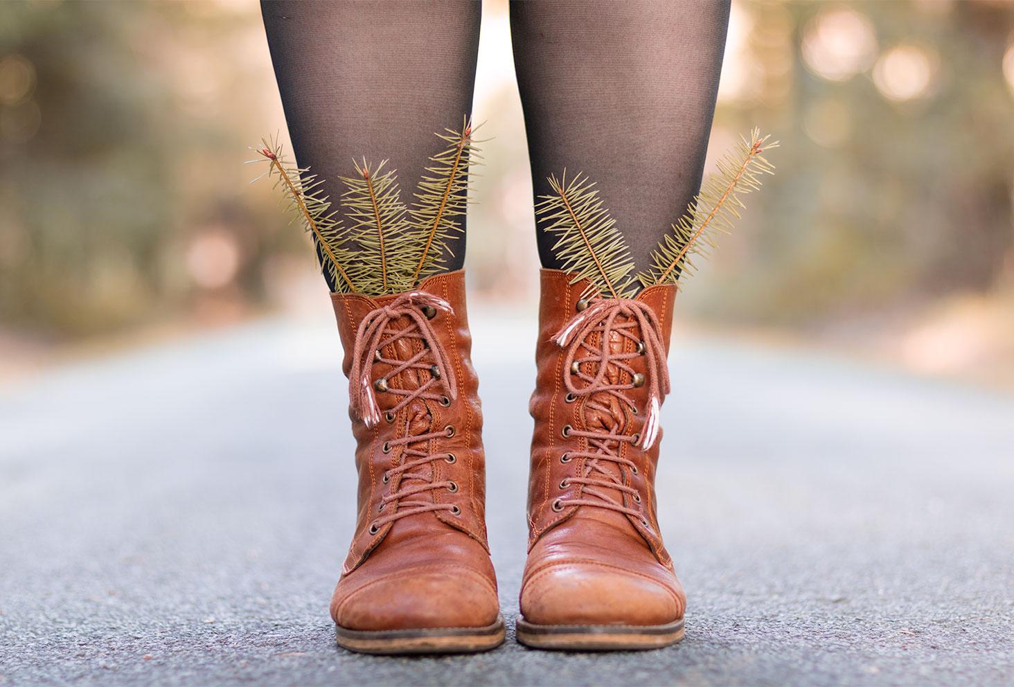 Zoom sur les boots vintage en cuir marron portées, des branches de sapin coincées à l'intérieur