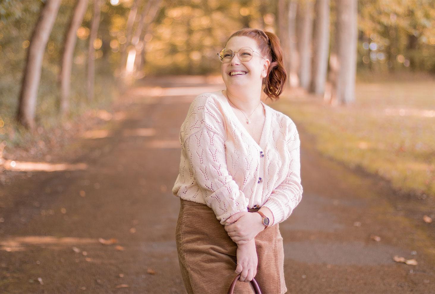 Zoom sur le gilet beige rosé porté, avec le sourire et les cheveux attachés