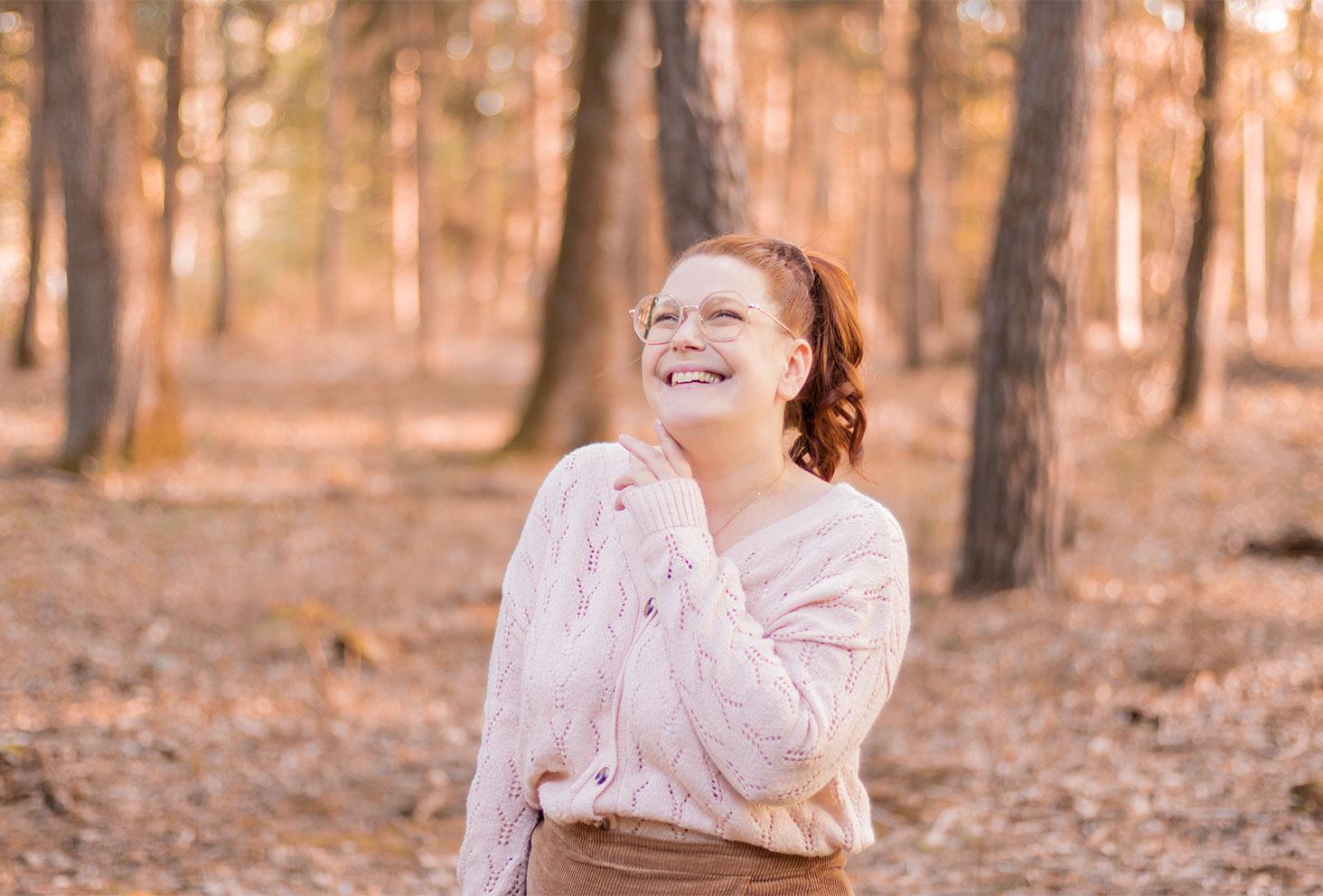 Zoom sur le pull beige rosé porté au milieu d'une forêt d'automne, avec le sourire et les cheveux attachés